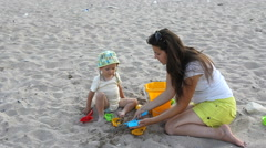Young mother and baby son playing together with colored sand toys, seashore Stock Footage