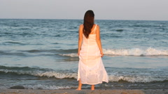 Beautiful woman with white dress, long hair in the wind admire sea, romantic - stock footage