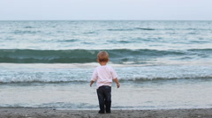 Amusing baby child take a seashell and throw off in sea, rising his shoulders - stock footage
