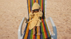 Amusing baby dressed with bathrobe on  chaise long try to arrange sunglasses - stock footage