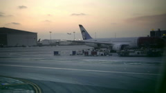 Airplane taking off in airport at sunset in 1080 HD Stock Footage