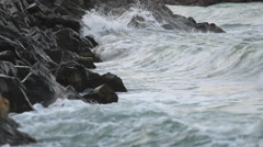 Sea waves breaking off the stones, stirred sea, before the storm - stock footage