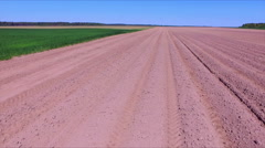 Flying over the ploughed field with rows of fresh soil - stock footage