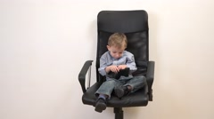 Little child sitting on business chair throwing off the money from the wallet Stock Footage