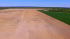 Flying over the ploughed field - stock footage