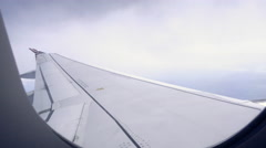Airplane window - passenger pov - wing of plane in air in 4K Stock Footage