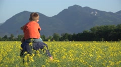 Father giving a piggy ride to little son looking to rape blossom field, mountain Stock Footage