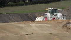Tractor and compactor working on site in field Stock Footage