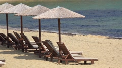 Straw umbrellas, wooden sunbeds, empty beach and blue waves Stock Footage