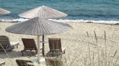 Straw umbrellas, lounge sunbeds on the beach and blue water Stock Footage
