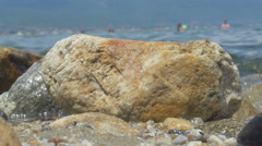 Stones in foreground, people bathing and swimming in blurred background. Sheyno. Stock Footage