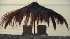Sunbeds and palm tree umbrella on beach at sunset Stock Footage