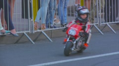 Child in a professional outfit riding a small motorcycle Stock Footage