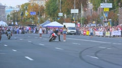 Motorcyclist revolves around the girl, keeping one foot on the ground Stock Footage