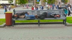 Two homeless man sleeping on a bench in identical poses Stock Footage