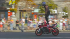 Motorcyclist rides, standing feet on the motorcycle tank, Christ, Stunt Riding Stock Footage