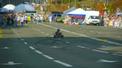 Little boy on a small motorcycle demonstrates to the public the ability to drive Stock Footage