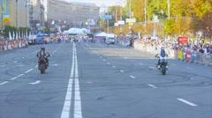 Trick riders demonstrate public wheelies on the rear wheel Stock Footage