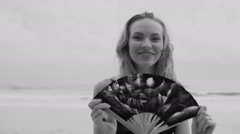 Sensual glamour woman in black bikini with hand fan on a beach Stock Footage