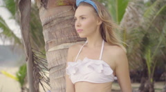 Pretty naturally looking woman on a beautiful summer day between palm trees - stock footage