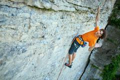 Male rock climber on the cliff Stock Photos