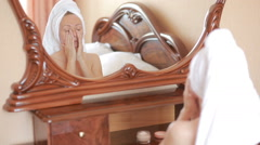 Woman applying mask moisturizing skin cream on face looking in mirror. Stock Footage