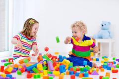 Kids playing with colorful blocks. Stock Photos