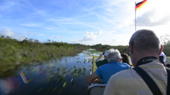 Everglades City Florida airboat ride fast with tourists riding on water wetla Stock Footage