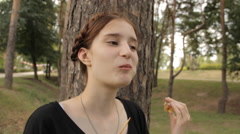 The girl eats candy apple and looks to the camera. Stock Footage
