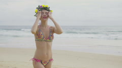 Beautiful blonde happy woman wearing colourful swimwear and wreath on a beach Stock Footage