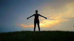 Girl doing exercise in sport at sunset background Stock Footage