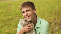 Guy holds a gray British cat Stock Footage