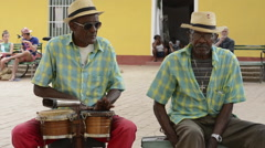 Trinidad Cuba in park with men playing music in park and singing band Stock Footage