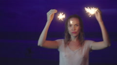 Closeup of happy woman with sparkler fireworks on the beach at night Stock Footage