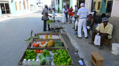 Cardes Cuba fruit seller on streets with locals sitting around on curb Stock Footage