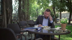 Businessman answers the phone and checks data during lunch. Steadicam shot. Stock Footage