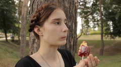 Beatiful girl eats candy apple. Zoom in and out. Stock Footage