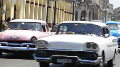 Hava Cuba old classic 1950's autos in traffic downtown near Capital with locals Stock Footage