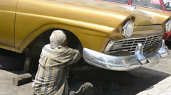 Hava Cuba a typical scene of a man repairing his old classic US 1950's auto to Stock Footage