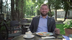 Businessman smiling to camera, during lunch. Steadicam shot. Stock Footage