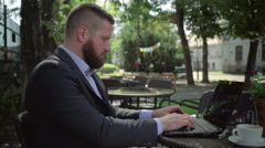 Businessman writing on laptop, outdoor. Steadicam shot. Stock Footage