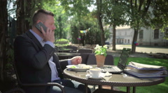 Businessman talking by phone during lunch. Steadicam shot. Stock Footage