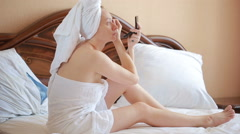 Beautiful woman plucking eyebrows. woman on the bed in the bedroom Stock Footage