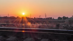 Timelaps sunset over a field along the railway Stock Footage