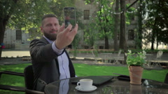 Businessman makes selfie during coffe break. Outdoor. Steadicam shot. Stock Footage