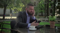 Bored businessman closes laptop and browsing smatphone. Outdoor. Steadicam shot. Stock Footage