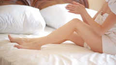 Girl on the bed to put a cream on legs. beautiful woman skin care Stock Footage