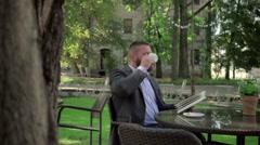 Businessman reading book during coffe break. Outdoor. Steadicam shot. - stock footage