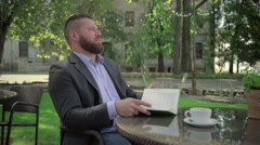 Businessman ends reading book during coffe break. Outdoor. Steadicam shot. - stock footage