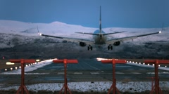 Plane landing at airport scenic landscape snowed mountains night from behind Stock Footage